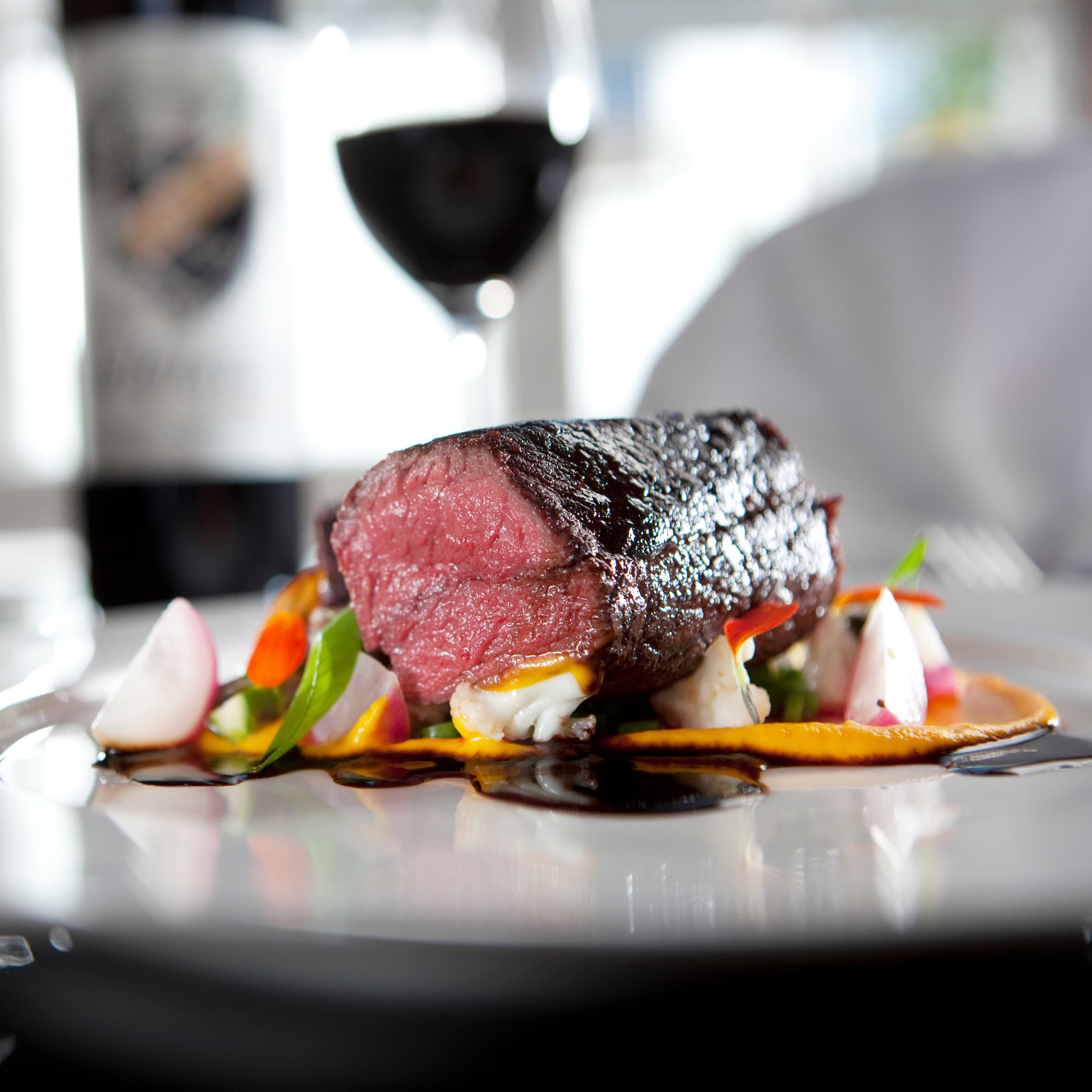 cook reindeer filet on a table with vegetables and a glass of wine