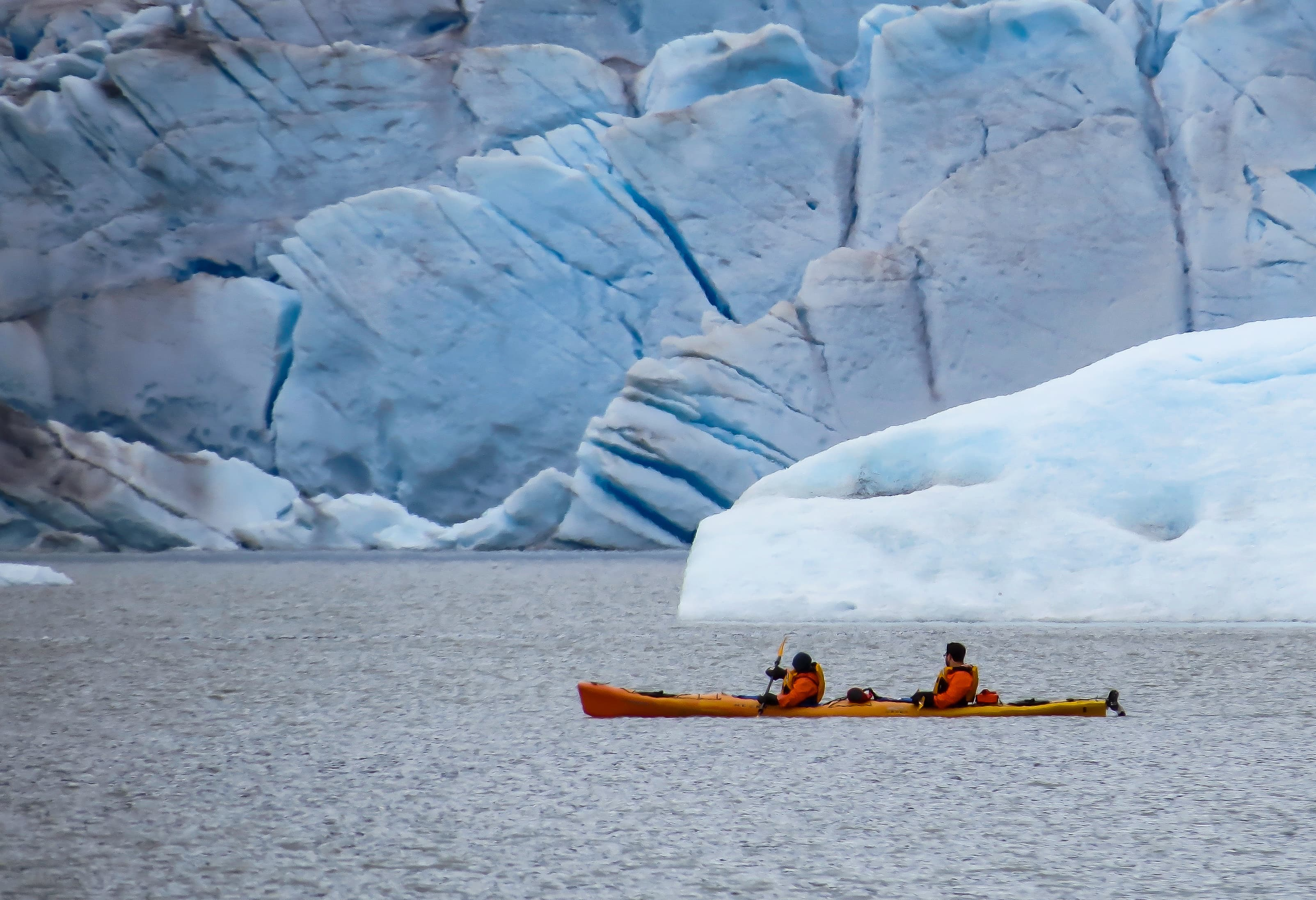 two people in a double kayak in the water next to a glacier
