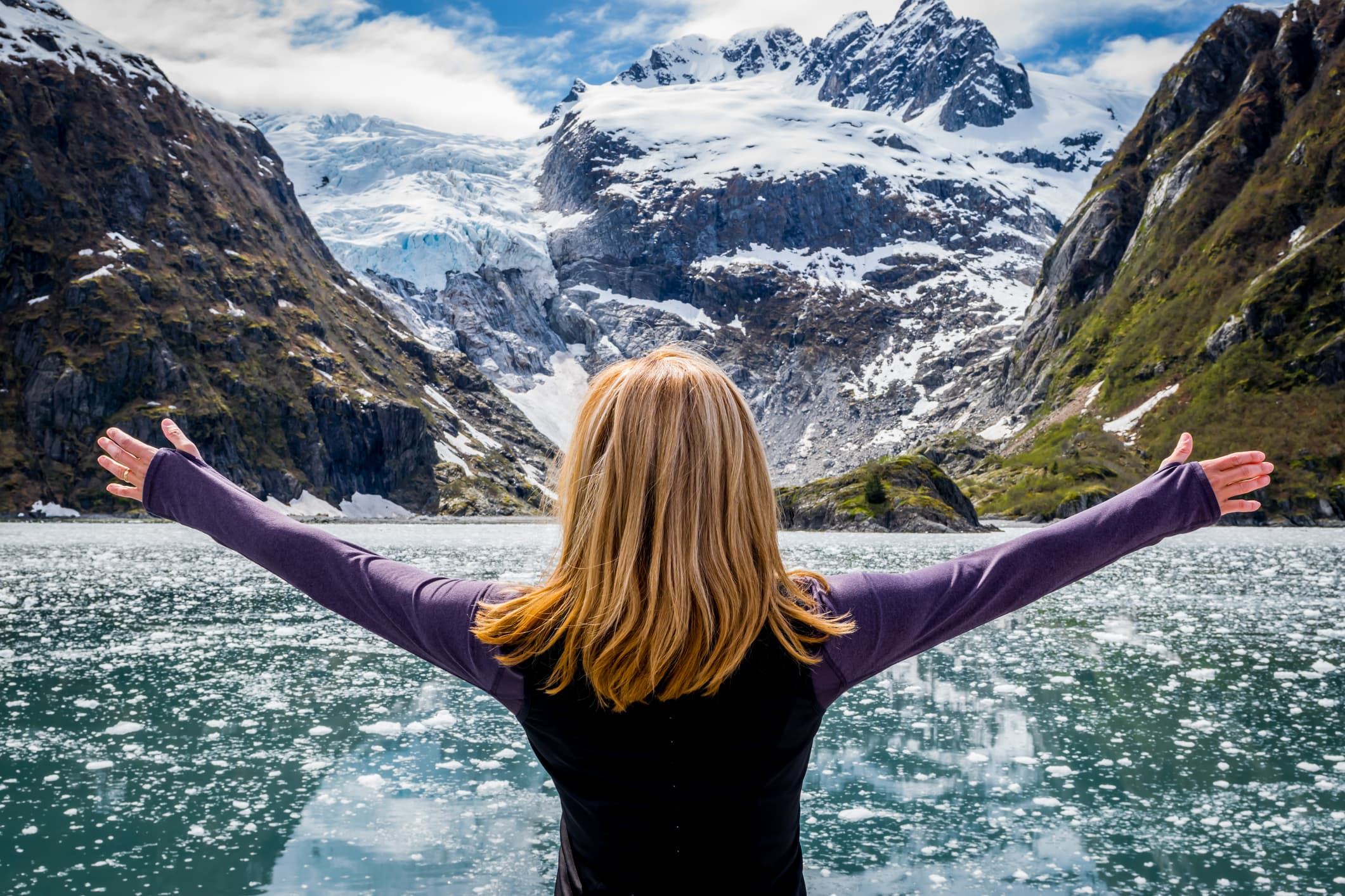 Woman looking at mountain range and glacier