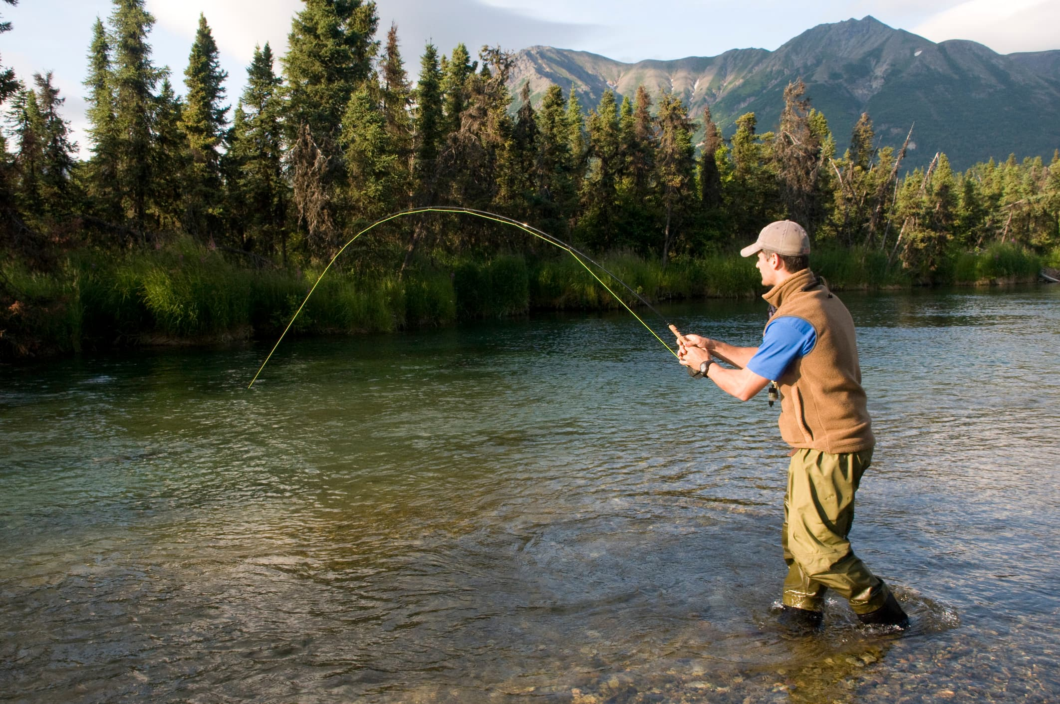 man with fishing pole standing in a river