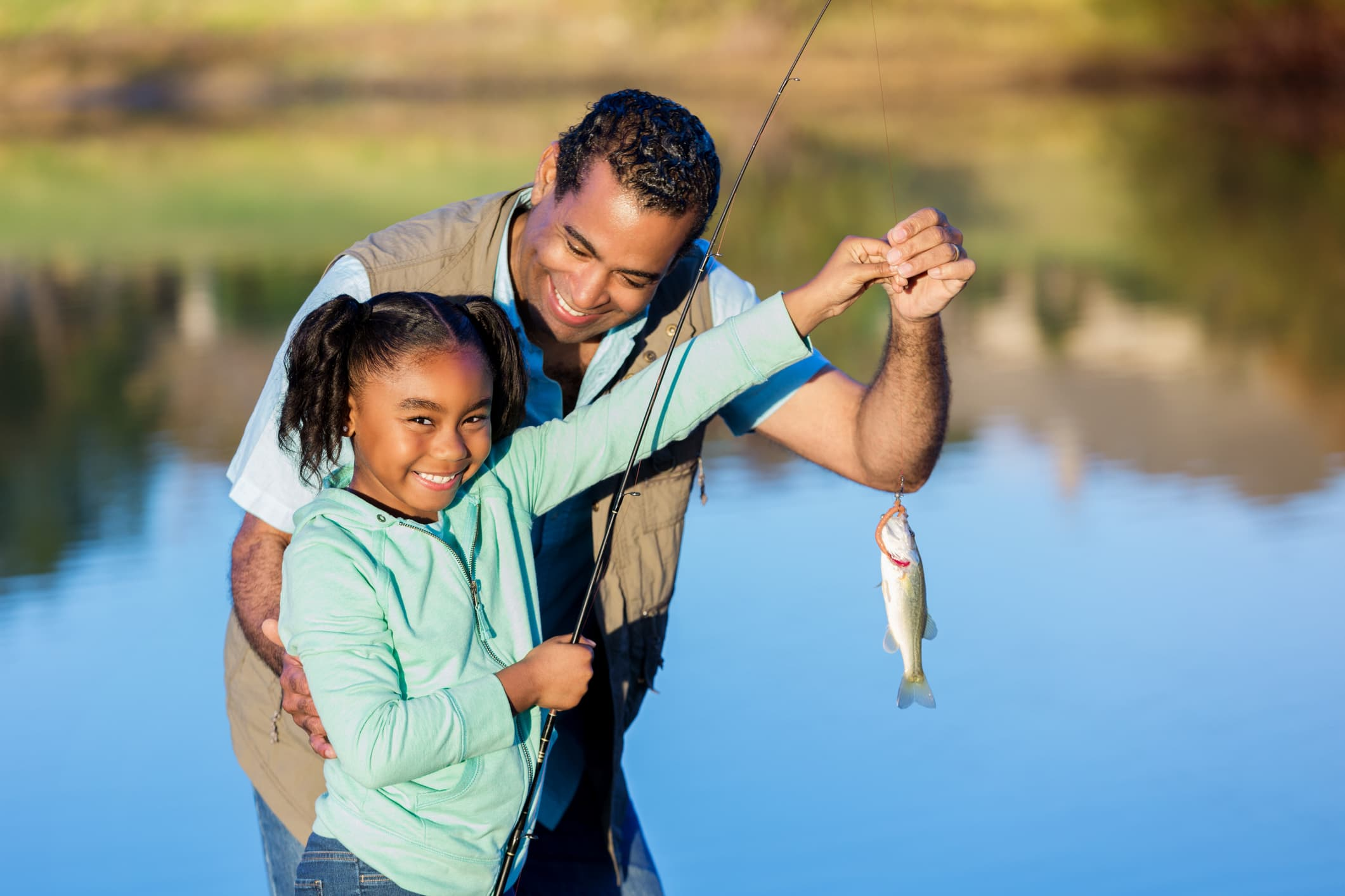 Proud girl shows off fish while fishing with granddad