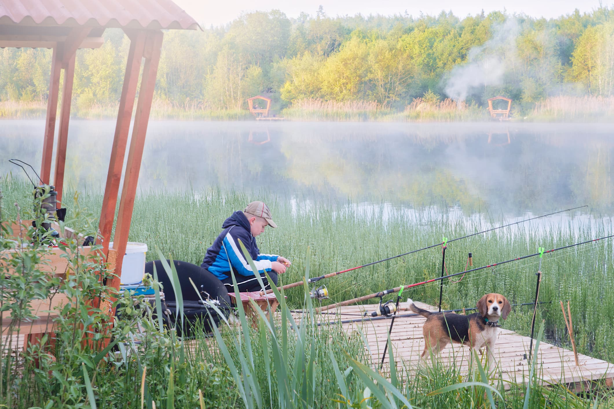 man and dog fishing on a dock