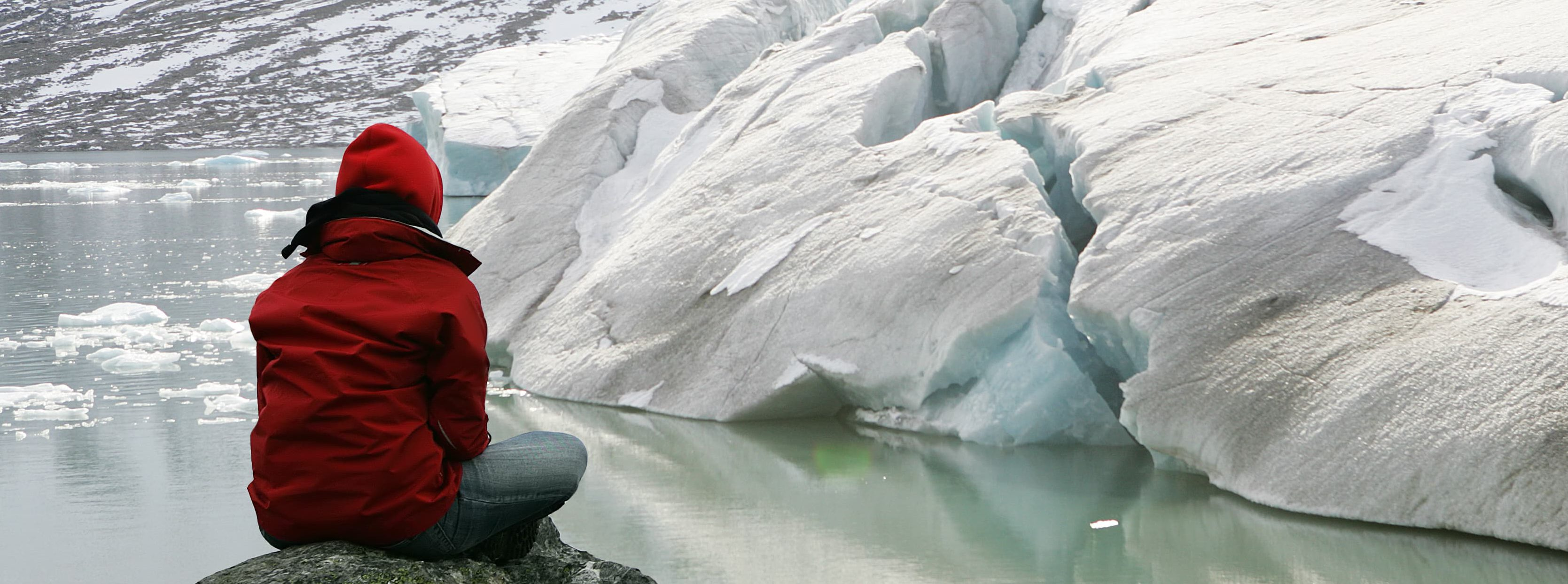 Woman sitting on a rock looking at glaciers