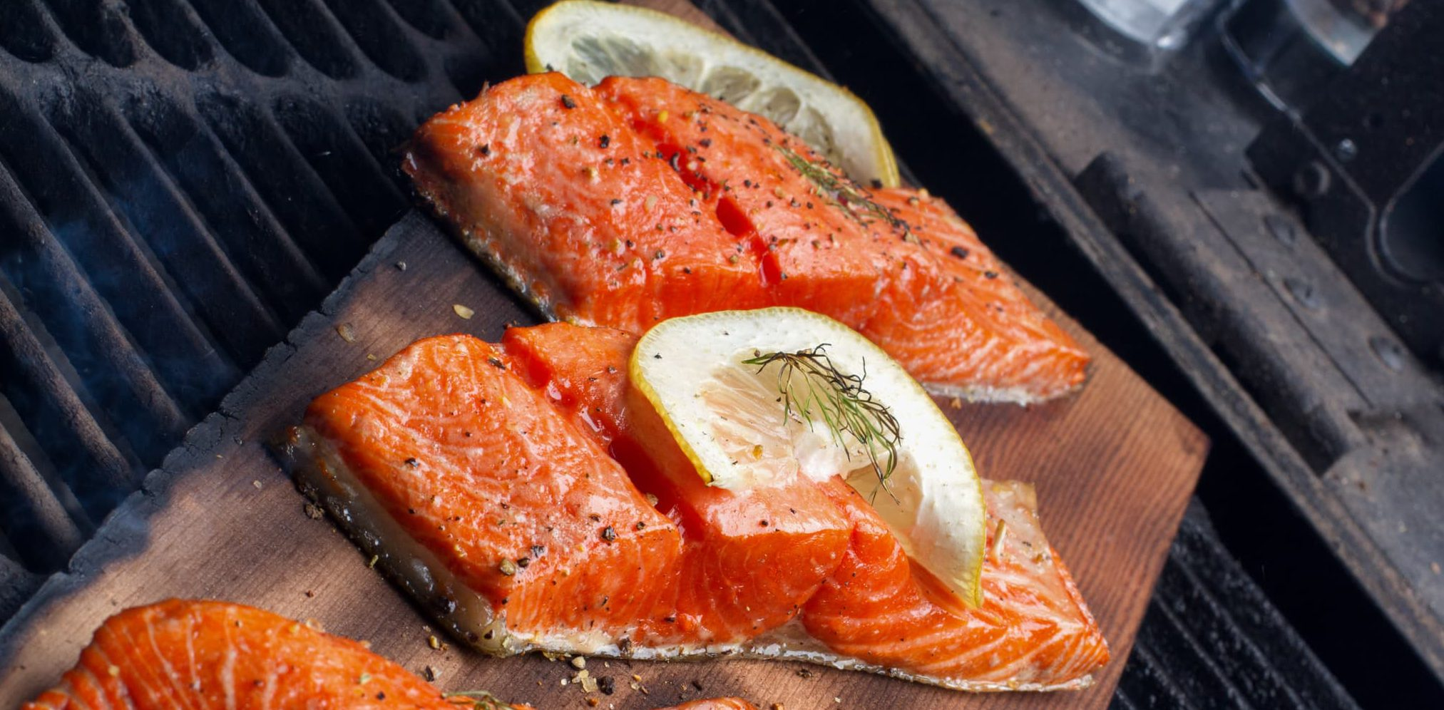 salmon fillets on a cedar plank on a grill with lemon