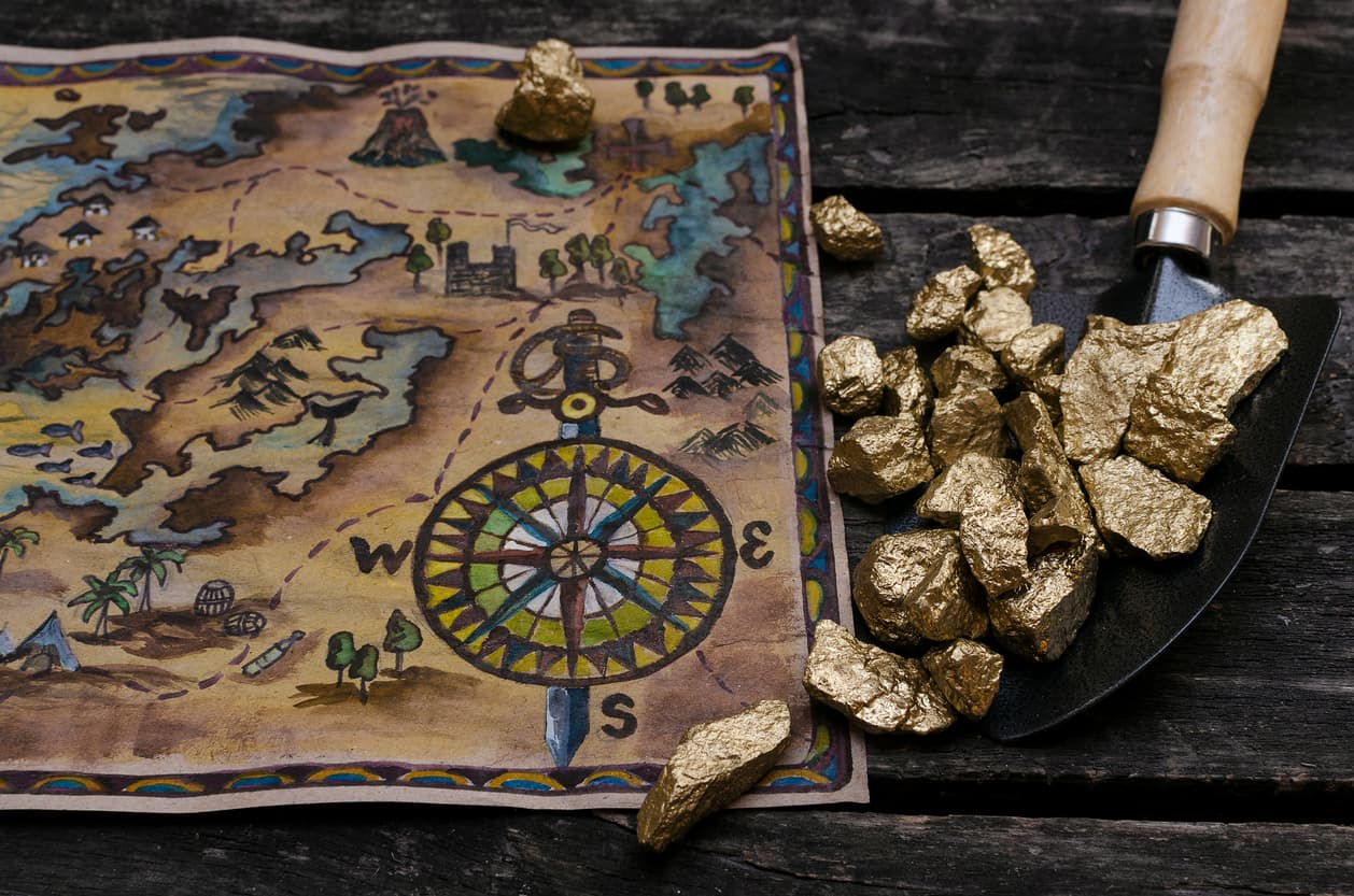 A map of Alaska with nuggets of gold, both of which are on a brown table.
